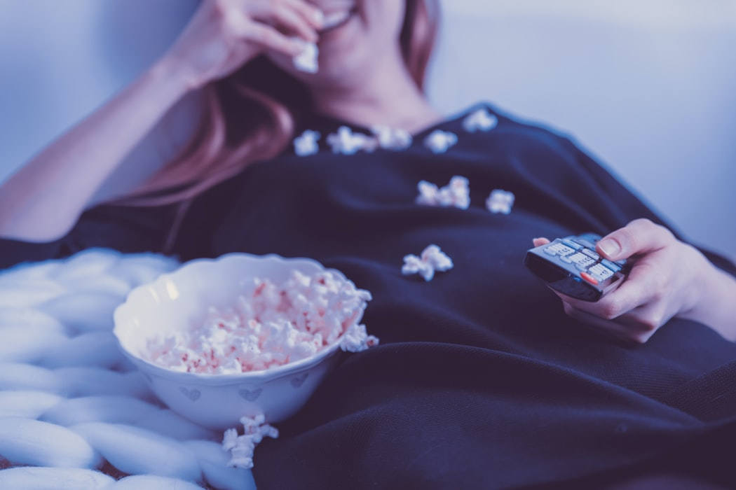 woman_lying_on_bed_while_eating_puff_corn_photo